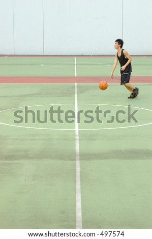 basketball court in muted tones. player with slight motion blur
