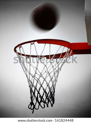 Basketball going into hoop and net with white background - stock photo
