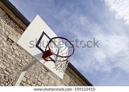 Basketball hoop against a cloudy sky. - stock photo