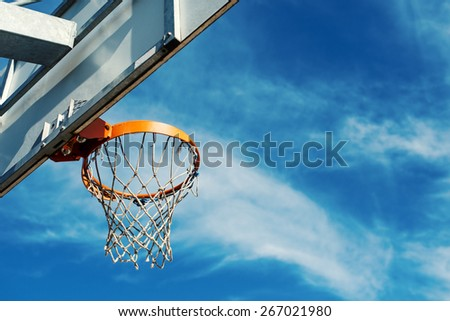 Basketball hoop against blue cloudy sky with copy space. - stock photo