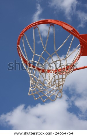 Basketball hoop against clouds, vertical