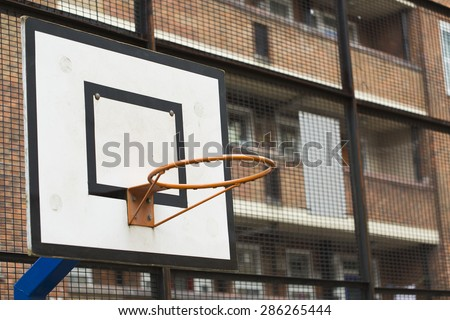 Basketball hoop and backboard on a residential living estate with flats in the background - stock photo