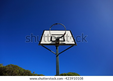 Basketball Hoop and Basketball Court against Blue Sky
