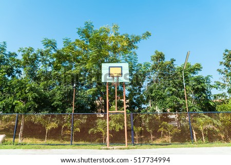 Basketball hoop in the park with green trees in background