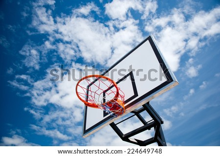 Basketball hoop on blue sky and clouds - stock photo