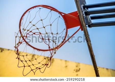 Basketball hoop under yellow wall & blue sky - stock photo