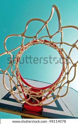 Basketball hoop with cage against the warm summer sky. - stock photo