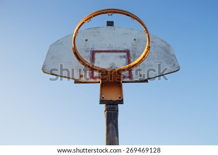 Basketball hoop without a net against a weathered wood backboard under a blue sky - stock photo