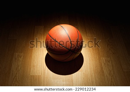 Basketball illuminated bright spotlight on wood court floor