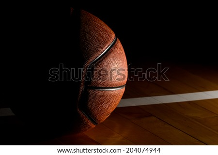 Basketball isolated on court black background with light effect  - stock photo
