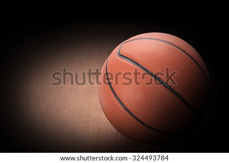 Basketball on hard wood dark background as a symbol of sport and exercise, leisure activities, team players with dribbling and passing the ball in a competitive match. This has clipping path. - stock photo