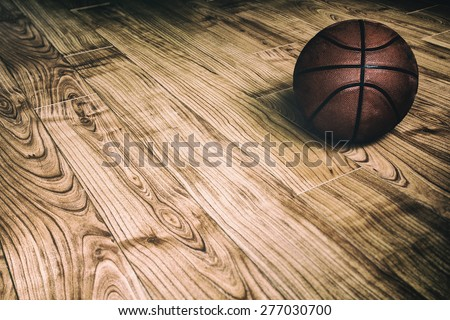 Basketball on Hardwood 2. A basketball laying on the ground of a hardwood court in a gymnasium. - stock photo