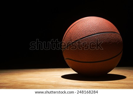 basketball on the hardwood in a spotlight - stock photo
