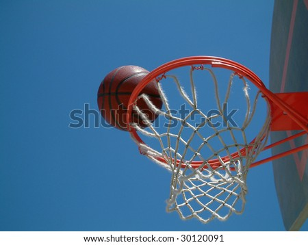 Basketball on the rim - stock photo