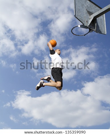 Basketball Player about to Slam Dunk. Concept of high flying - stock photo