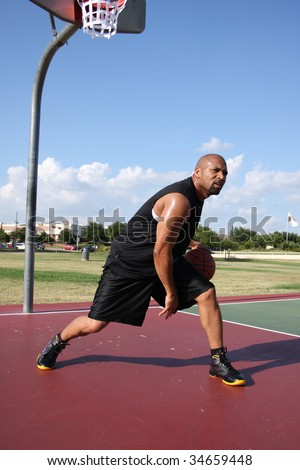 Basketball player dribbles between legs - stock photo