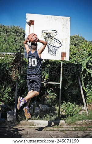 basketball player dunking in the park - stock photo