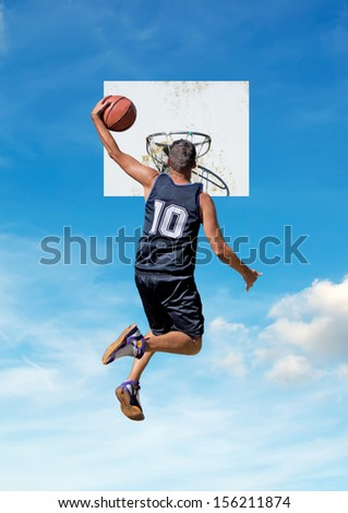 basketball player dunking with a sky in the background - stock photo