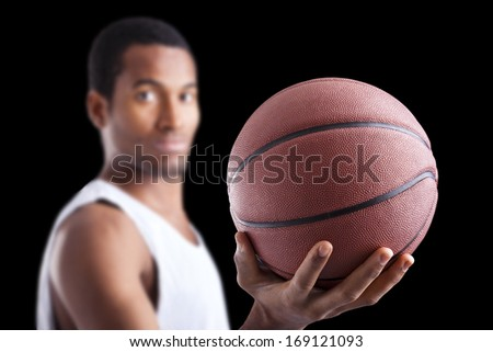 Basketball player holding a ball against dark background