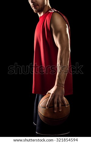 Basketball player holding ball isolated on black background - stock photo