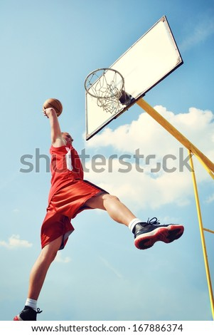Basketball player in action flying high and scoring - stock photo