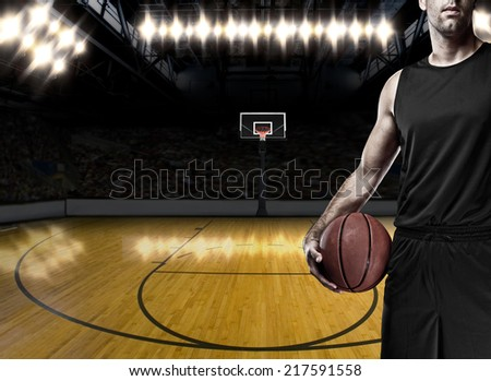 Basketball player on a  black uniform, on a basketball court. - stock photo