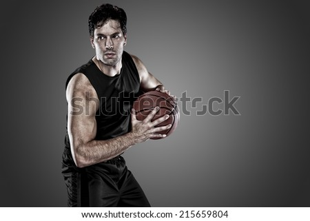 Basketball player on a  black uniform, on a black background. - stock photo