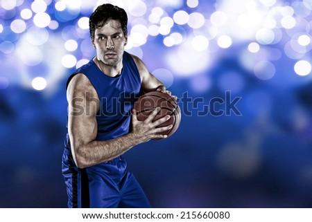 Basketball player on a  blue uniform, on a blue lights background. - stock photo