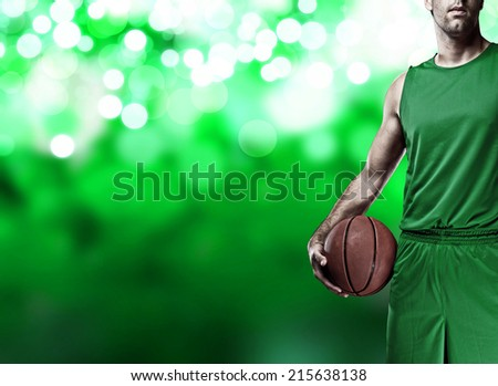 Basketball player on a  green uniform, on a green lights background. - stock photo