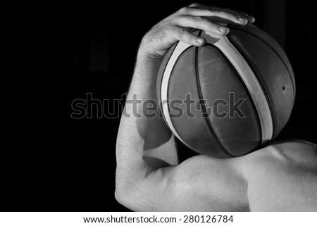 Basketball player portrait on basketball court holding ball - stock photo