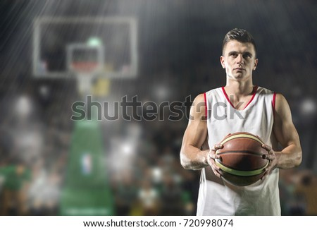 Basketball player portrait  on basketball court holding ball in front of modern basketball arena
