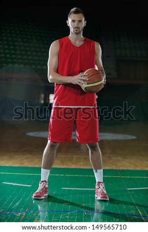 Basketball player portrait  on basketball court holding ball with black isolated background - stock photo