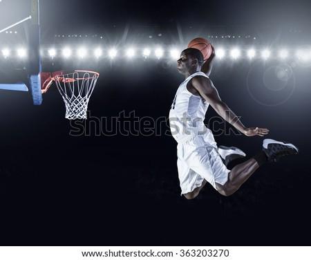Basketball Player scoring an athletic, amazing slam dunk - stock photo