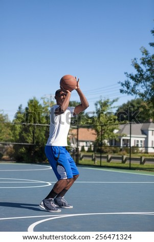 Basketball player shooting the ball at the basket on an outdoor court. - stock photo