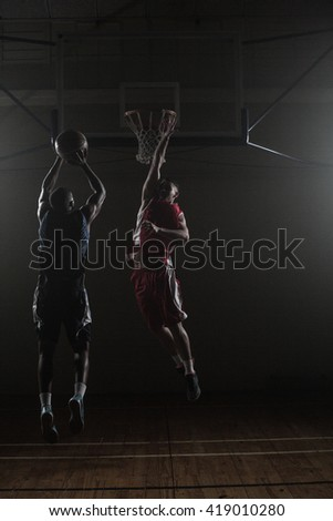 Basketball player shooting while a defender trying to block him in a gymnasium - stock photo