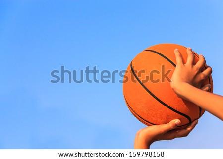 Basketball player shooting with blue sky - stock photo