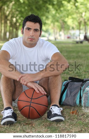Basketball player sitting - stock photo