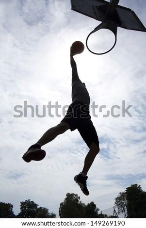 Basketball Player Slam Dunk Silhouette - stock photo