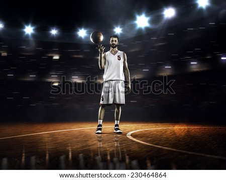 Basketball player spinning ball in gym - stock photo