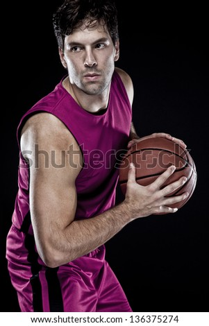 Basketball player with a ball in his hands and a pink uniform. photography studio. - stock photo