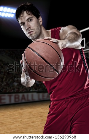 Basketball player with a ball in his hands and a red uniform. photography studio. - stock photo