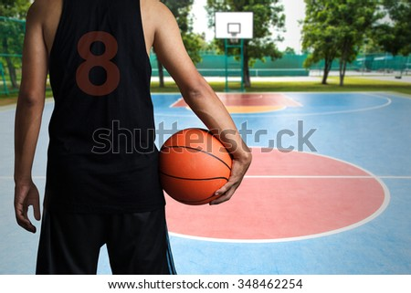 Basketball player with a ball, outdoor basketball court  - stock photo