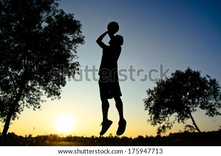 Basketball player with silhouette sunset background as Olympic sport concept