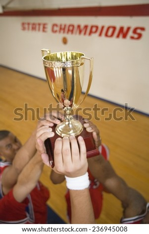 Basketball Players Holding Trophy - stock photo