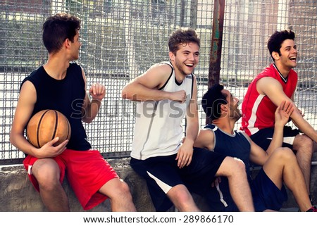 basketball players take a break sitting on a low wall - stock photo