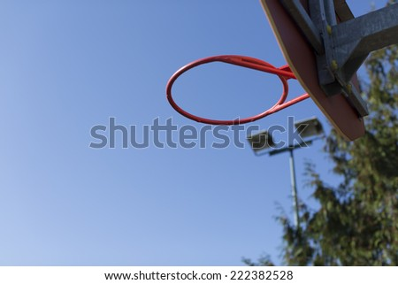 Basketball ring with no net on an outdoor basketball court in the sunlight - stock photo