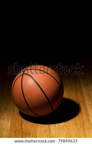 Basketball sitting on basketball court in the spotlight. - stock photo