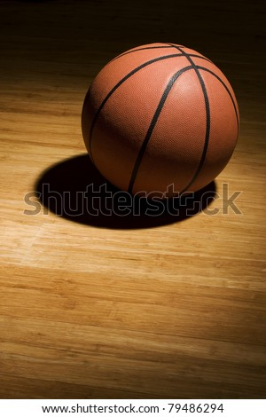 Basketball sitting on hardwood floor in spotlight.