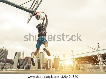 Basketball street player making a rear slam dunk. New york and Manhattan buildings in the background - stock photo