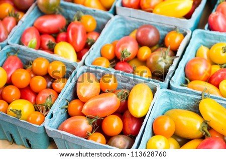 Baskets of colorful cherry tomatoes on display at the market - stock photo